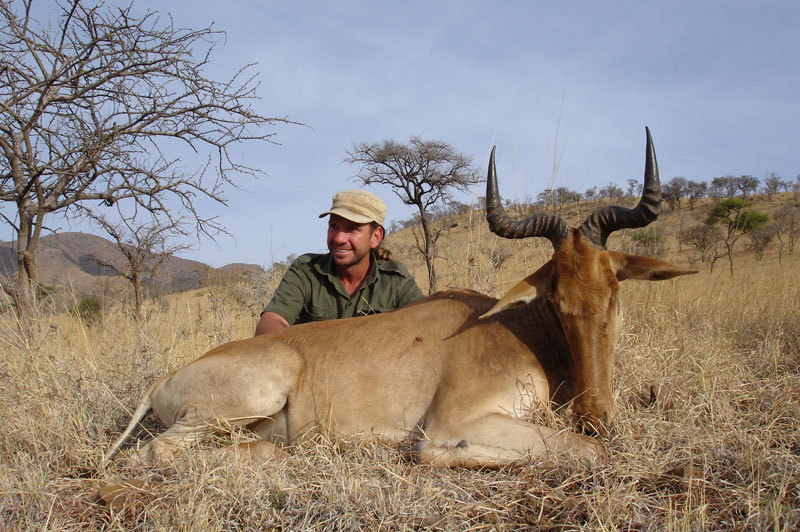 The writer's guide, the South African, Schalk Tait, poses with wrier's good representative Coke's hartebeest on the slopes of Simangore Mountain near Mto-wa-Mbu in Tanzania's Masailand.