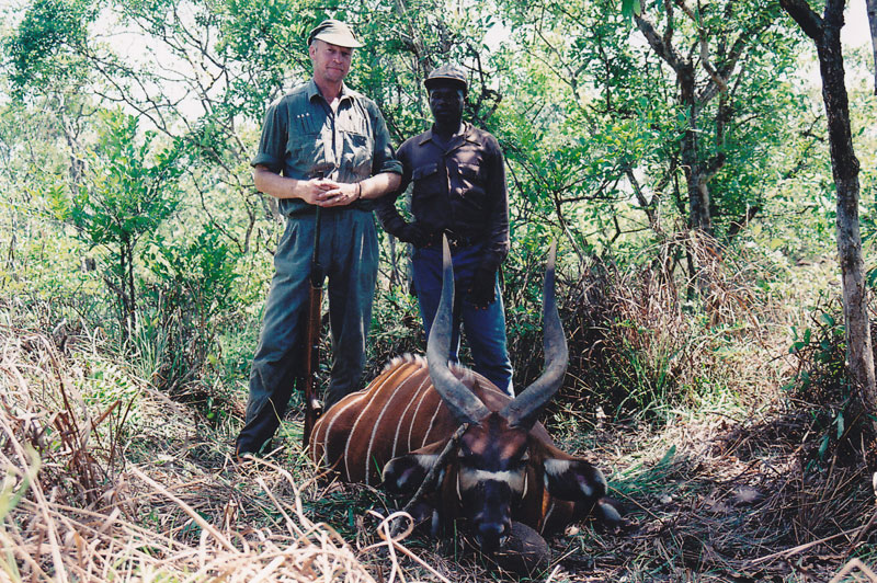 The author and Martin, son of the local Zande chief, elephant poacher and the best tracker the author has ever hunted with, stand next to the author's first bongo bull as mentioned in the story.