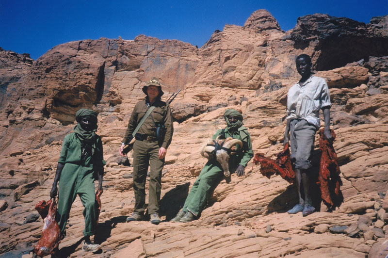 Climbing down from one of the massifs in the Ennedi Mountain range with the author's first Barbary sheep. From L to R: Egray Djeme, the author, Gaille Atim, a tracker from Gos-Beida and a local Arab boy, Omar Kore, who acted as our water carrier.