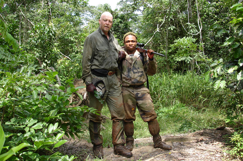 The author and his gun bearer, Mombateau, carrying the author's custom made .416 Rigby topped by a 1.5-6x42  Zeiss Diavari low light scope, an important piece of equipment in the dark rain forest.