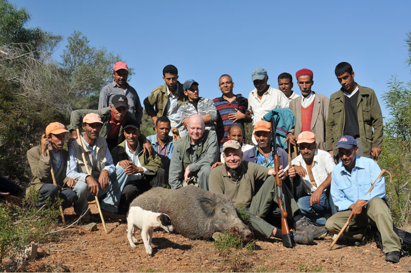 Some of the beaters and a puppy in training surround the author and Hans Siege with the huge Barbary wild boar or 'Keiler' as our German friends called it, which Hans shot on our second day. It was by far tyhe biggest pig we saw in our week long shoot.