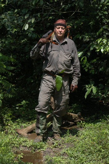 PHF carrying his.416 Rigby with a waterproof scope cover out of the Cameroon rain forest where it had just stopped raining. The green leaf tucked into his belt was given him each morning by the pygmies with whom he hunted as a good luck charm to keep him safe.